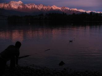 Ted skimming a stone over Lake Wakatipu: Aardwolfs Ice Hockey Club Southern Migration.
