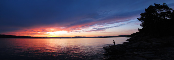 Panorama of sunset near Ingierstrand just outside of Oslo, Norway. Irene on the shore.