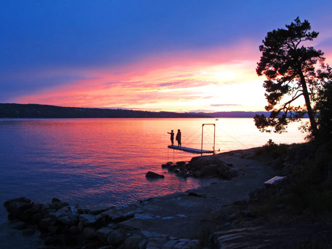Beautiful sunset near Ingierstrand, just outside of Oslo, Norway. Irene and Hilde on jetty.